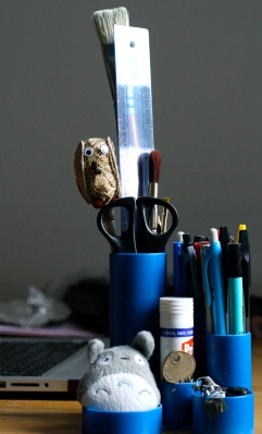 Blue desk tidy, featuring a blue ruler and some blue pens. Also the weird wicker owl thingy and Totoro.