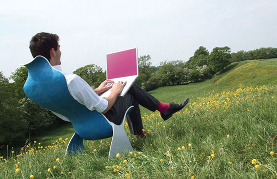 Man sitting in a modernist chair in a field of buttercups pretending to type on a laptop with a blank pink screen