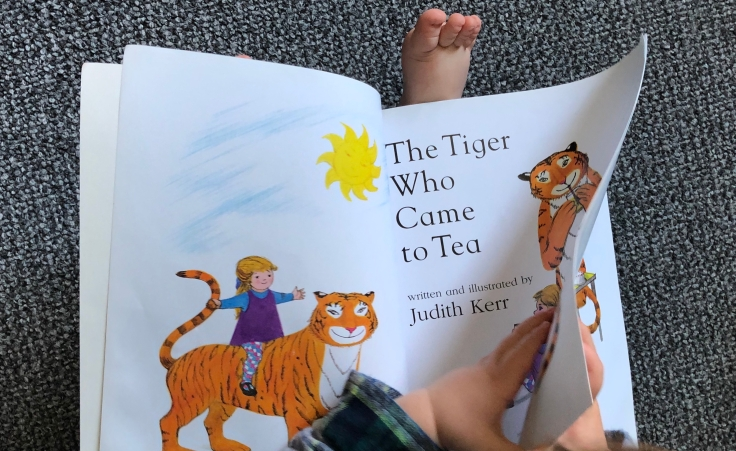 small hands turning the page of a book with a picture of a tiger and the title 'the tiger who came to tea'